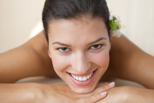 women with young skin smiling and lying on massage table